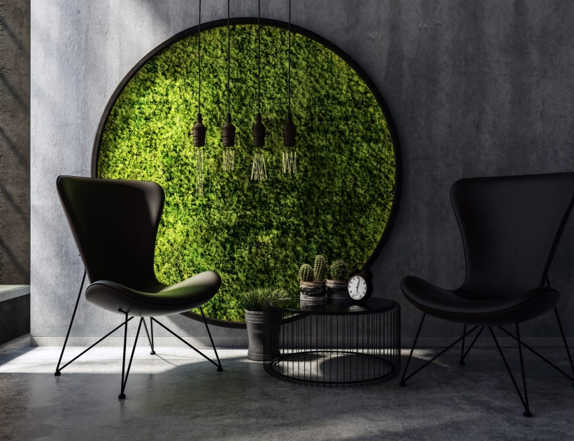 Two chairs with small table standing by round moss wall art
